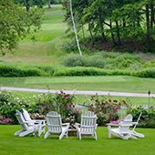 Chairs on lawn overlooking rose garden and golf course