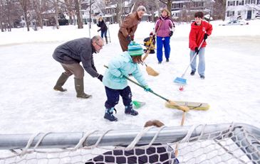 Residents playing broomball on outdoor skating rink
